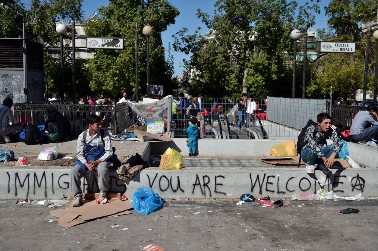 "Young Afghanis sit next to a slogan reading ""Immigrants, you are welcome"", as hundreds of migrants evacuate their camp at Victoria square in central Athens, before being transferred to a former Olympic hall, on October 1, 2015. Hundreds of mainly Afghan migrants had set up tents on Victoria Square in recent days, prompting protests from the city of Athens and local residents. Greek authorities on October 1, 2015 hastily reopened a derelict sports hall from the Athens 2004 Olympics to house hundreds of migrants who were sleeping on the streets of the capital. (Louisa Gouliamaki/AFP/Getty Images)"