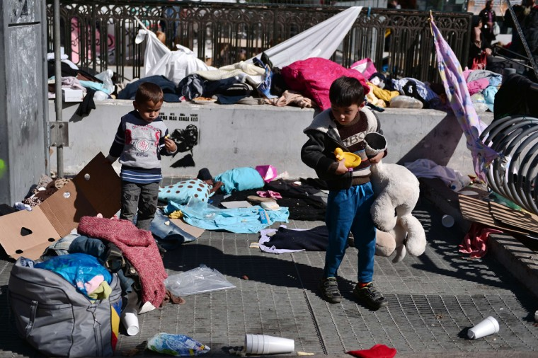 Young migrant children look for their toys as hundreds of migrants evacuate their camp of Victoria square in central Athens, before being transferred to a former Olympic hall, on October 1, 2015. Hundreds of mainly Afghan migrants had set up tents on Victoria Square in recent days, prompting protests from the city of Athens and local residents. Greek authorities on October 1, 2015 hastily reopened a derelict sports hall from the Athens 2004 Olympics to house hundreds of migrants who were sleeping on the streets of the capital. (Louisa Gouliamaki/AFP/Getty Images)