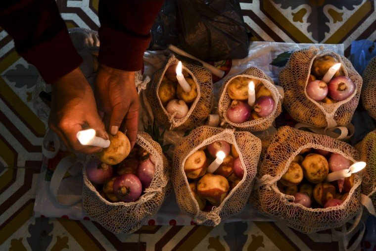 "A Colombian indigenous woman of the Misak ethnic group lights a candle as she takes part in an offering ceremony at Our Lady of Chiquinquira church in Silvia, department of Cauca, Colombia, on November 1, 2015, during the celebration of All Saints Day. The Misaks are, of the hundred indigenous groups that inhabit Colombia, the ones who have their customs best preserved, including a colorful ceremony of offerings to the dead, closely related to the cult of ""Mother Earth"" and the New Year. The Day of the Offerings is celebrated between November 1 and 2, when the favorite food of the dead is prepared to receive their spirits and harmonize the territory. (Luis Robayo/Getty Images)"
