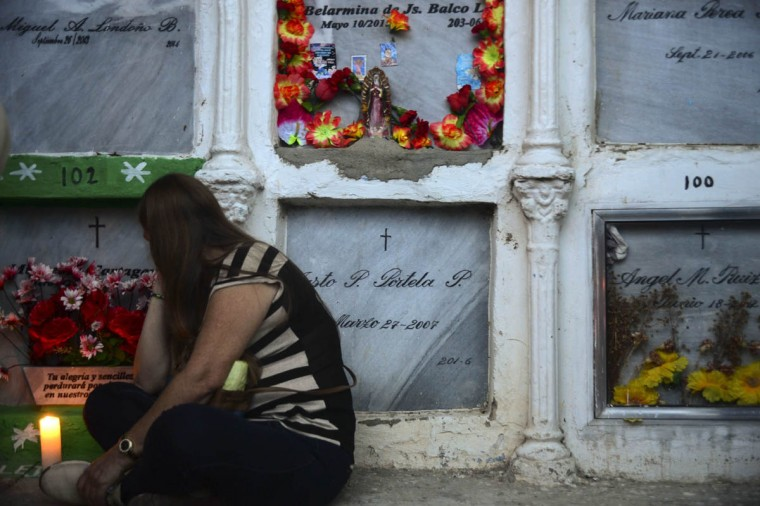 Faithful participate in a ceremony at the San Javier cemetery in the Comuna 13 shantytown in Medellin, Antioquia department, Colombia during the celebration of All Saints Day, on November 2, 2015. (Raul Arboleda/Getty Images)