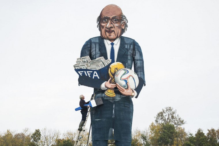 British artist Frank Shepherd of the Edenbridge Bonfire Society poses putting the finishing touches to a giant effigy of the suspended president of FIFA Sepp Blatter in Edenbridge, Kent, southeast England, on November 4, 2015 that will be exploded and burned at this year's Bonfire Night celebrations. The Edenbridge Bonfire Society has been making fun of public figures for 20 years by building and exploding a second 'celebrity Guy' effigy alongside their traditional figure of Guy Fawkes as part of the Bonfire Night celebrations in the town. Blatter was suspended from his role as FIFA president in October 2015 by FIFA's independent ethics committee for 90 days as part of a wide-ranging investigation into corruption at the heart of world football's governing body. (AFP Photo/Jack Taylor)