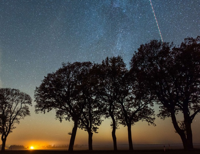 Light traces of an airplane cross the sky that is spangled with stars of the milky way on November 3, 2015 near Petersdorf, northeastern Germany. The peak of the Leonids meteor shower is expected for mid-November 2015. (AFP Photo/Patrick Pleul)