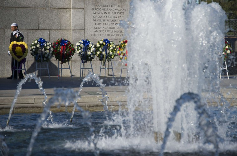 A sailor stands near wreaths during a ceremony at the World War II Memorial on Veteran's Day in Washington, DC, November 11, 2015. (AFP Photo/Jim Watson)