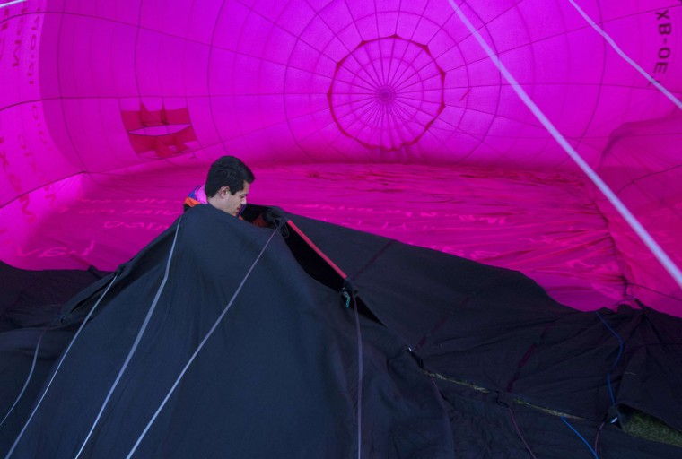 A man inflates a hot air balloon during the International Balloon Festival at the Metropolitan Park in Leon, Guanajuato state, Mexico on November 13, 2015. (HECTOR GUERRERO/AFP/Getty Images)