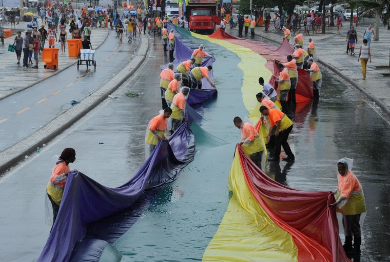 Workers fold a rainbow flag as a downpour falls during an LGBT Pride parade along Copacabana beach in Rio de Janeiro, Brazil, on November 15, 2015. (TASSO MARCELO/AFP/Getty Images)