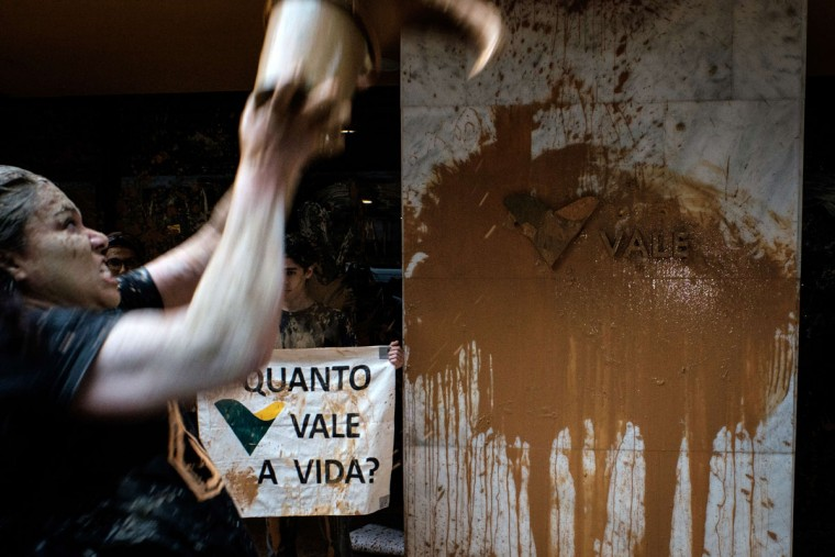 "A woman throws muddy water on the façade of Brazilian mining company Vale headquarters next to a sign reading ""How much does a life cost?"" during a protest in Rio de Janeiro, Brazil, on November 16, 2015. The bursting of two dams at a mine operated by Brazilian company Samarco - equally owned by Vale and Australian BHP Billiton- unleashed torrents of waste that flattened a village in Minas Gerais State on November 5 killing ten people. Brazilian mining firm Samarco promised Monday to pay at least $260 million for damage from the bursting, prosecutors said. (YASUYOSHI CHIBA/AFP/Getty Images)"