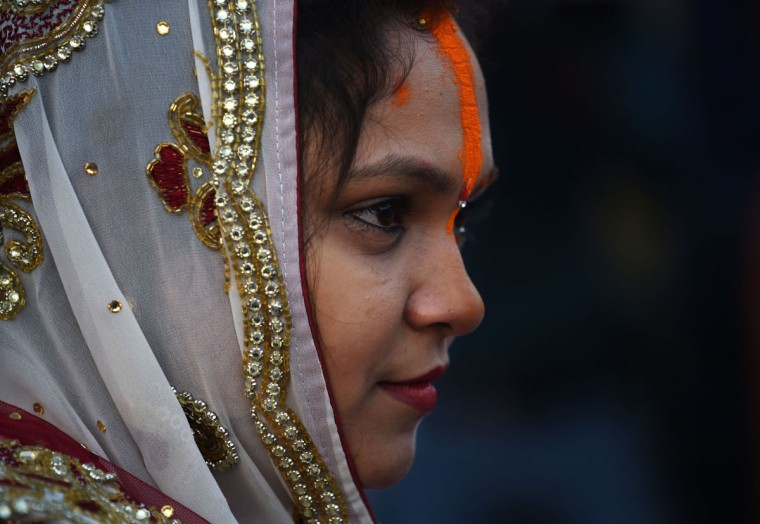 An Indian Hindu devotee looks on after offering prayers during the Chhath festival on the banks of the river Yamuna in New Delhi on November 17, 2015. Chhath festival, also known as Surya Pooja (worship of the sun), is observed in eastern parts of India where homage is paid to the sun and water Gods eight days after Diwali, the festival of lights. During Chhath festival, devotees undergo a fast and offer water and milk to the Sun God at dawn and dusk. (AFP Photo/Sajjad Hussain)