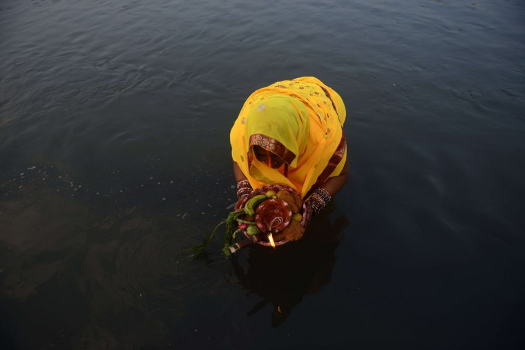 A Nepalese Hindu woman holds offerings as she worships the sun in the Bagmati River in Kathmandu on November17, 2015, during the Chhath Festival which honours the sun god. People pay their respects to both the rising and setting sun during the Chhath festival when people express their thanks and seek blessings from the forces of nature. (AFP Photo/Prakash Mathema)