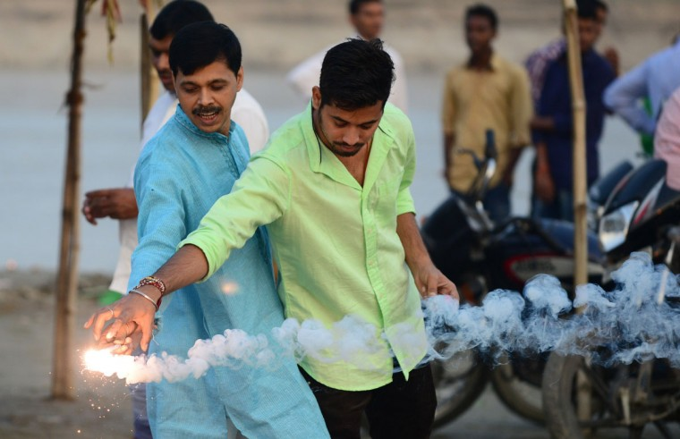 Indian devotees let off firecrackers during the Chhath festival in Allahabad on November 17, 2015. Devotees pay obeisance to both the rising and the setting sun during the Chhath festival when people express their thanks and seek the blessings of the forces of nature, mainly the Sun and the River. (AFP Photo/P /sanjay )