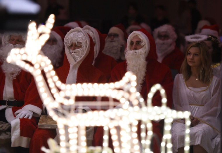 Men dressed as father christmas and women dressed as angels attend the annual meeting of volunteer Santa Clauses and Angels in Berlin November 28, 2015. (AFP Photo/Tobias Schwarz)