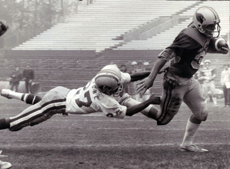 Calvert Hall's John Boddiford eludes Loyola defender Kevin Boone to score third of four touchdowns the unbeaten Cardinals chalked up in 28-0 Thanksgiving Day victory over the Dons at Memorial Stadium. It helps cap an 11-0 season for the top-ranked Cardinals. (Lloyd Pearson/Baltimore Sun, 1979)