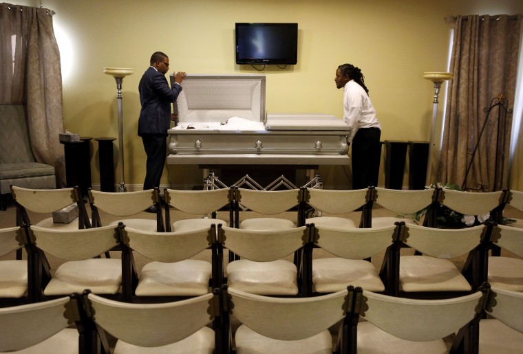 In this Oct. 16, 2015 picture, funeral director John Williams, left, closes a casket containing the remains of a man who died of natural causes in his Baltimore funeral home. Burying bodies is s a passion Williams inherited from his grandfather. Since he was a child, Williams said he's wanted to be an undertaker, to honor the dead and comfort grieving families. Guiding those who've lost loved ones gives him a sense of purpose. (AP Photo/Patrick Semansky)