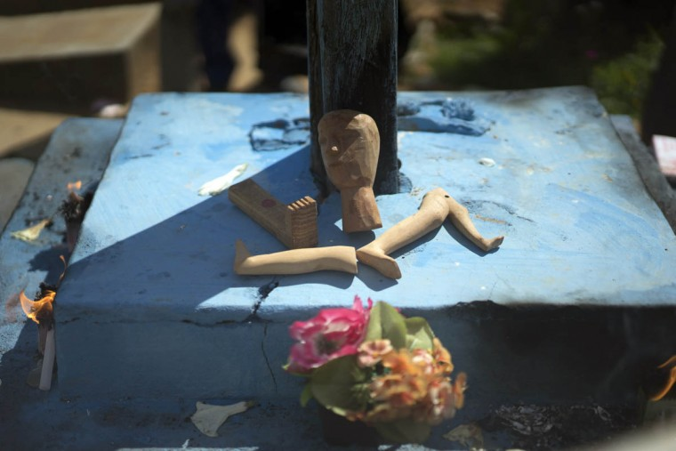 Wooden body parts left by believers lay next to a cross at the Perpetuo Socorro cemetery during Day of the Dead celebrations in Juazeiro do Norte, Brazil, Monday, Nov. 2, 2015. People leave behind items like this as a way to give thanks for what they believe to be answered prayers and as a public testimony of gratitude. (Leo Correa/AP photo)