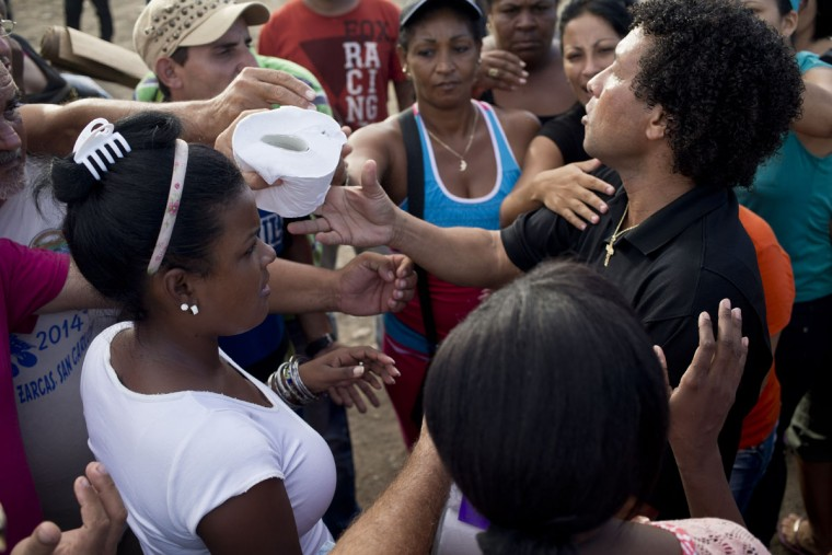"A Costa Rican hands out rolls of toliet paper to Cuban migrants outside the immigration office in PeÒas Blancas, Costa Rica, Tuesday, Nov. 17, 2015. Costa Rican Foreign Minister Manuel Gonzalez said in a radio interview Tuesday that there are nearly 2,000 people currently at the border being blocked by Nicaraguan soldiers from entering the country. He proposed the creation of a ""humanitarian corridor"" for Cubans transiting Central America. (AP Photo/Esteban Felix)"