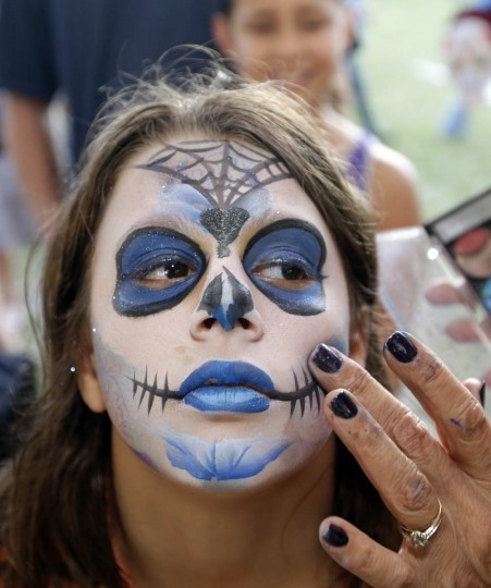 Breanna Keirn, 10, has her face painted as she celebrates the Day of the Dead, Monday, Nov. 2, 2015, in Fort Lauderdale, Fla. The event honors Mexican traditions where the dead are honored by their loved ones. (Alan Diaz/AP photo)