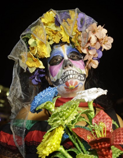 A South Floridian in costume celebrates the Day of the Dead, Monday, Nov. 2, 2015, in Fort Lauderdale, Fla. The event honors Mexican traditions where the dead are honored by their loved ones. (Alan Diaz/AP photo)