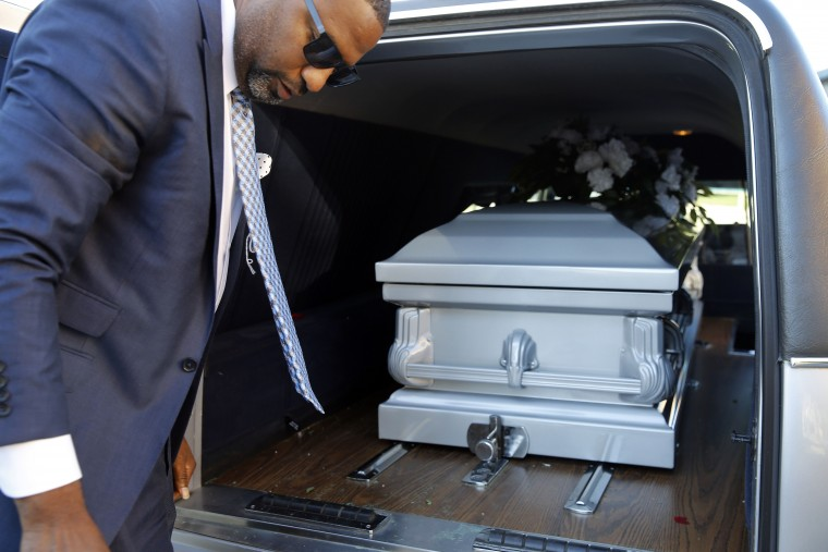 In this Oct. 16, 2015 picture, funeral director John Williams turns away after placing a casket containing the remains of a man who died of natural causes in a hearse in Baltimore. Coming off of the most violent year in the city's recent history, Williams has buried more bodies -- many of them young black men, many gunned down in the city's west side -- than ever before. In a normal month, he might do three funerals. This past summer, he buried two people a week. Some died naturally, of illness or old age. Most showed up pierced by knives or bullets. (AP Photo/Patrick Semansky)