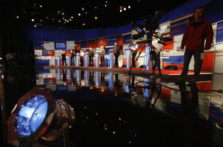 Workers stand in at the candidate's podiums in preparation for Tuesday's Republican debate, Monday, Nov. 9, 2015, in Milwaukee. (AP Photo/Morry Gash)