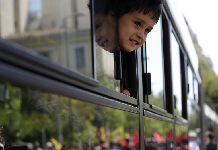A boy looks out of a bus window as he leaves with his family from Victoria square, where hundreds migrants and refugees stay temporarily before trying to continue their trip to more prosperous northern European countries, in Athens on Thursday, Oct. 1, 2015. Authorities in Greece have reopened a disused Galatsi Olympic Hall as police escorted buses carrying about 500 people, mostly from Syria and Afghanistan. (AP Photo/Thanassis Stavrakis)