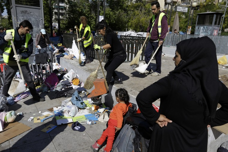 Municipality workers clear Victoria square, where hundreds migrants and refugees stay temporarily before trying to continue their trip to more prosperous northern European countries, in Athens on Thursday, Oct. 1, 2015. Authorities in Greece have reopened a disused Galatsi Olympic Hall as police escorted buses carrying about 500 people, mostly from Syria and Afghanistan. (AP Photo/Thanassis Stavrakis)