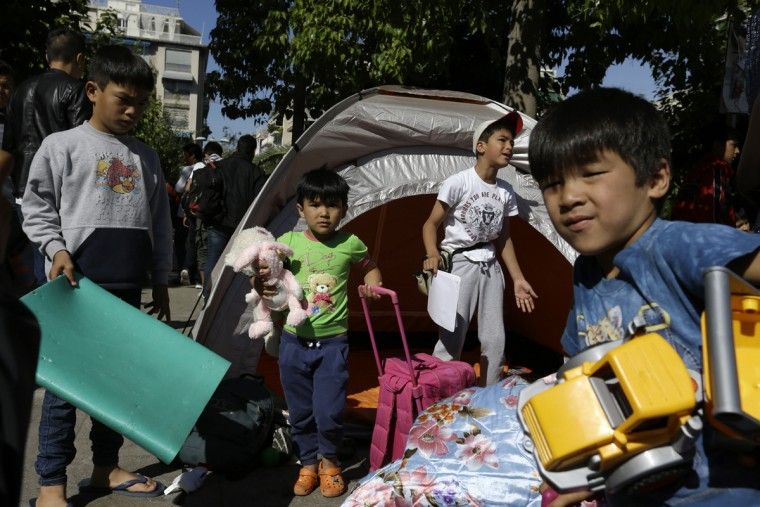 Children carry toys and bags leave from their family's tent at Victoria square, where hundreds migrants and refugees stay temporarily before trying to continue their trip to more prosperous northern European countries, in Athens on Thursday, Oct. 1, 2015. Authorities in Greece have reopened a disused Galatsi Olympic Hall as police escorted buses carrying about 500 people, mostly from Syria and Afghanistan. (AP Photo/Thanassis Stavrakis)