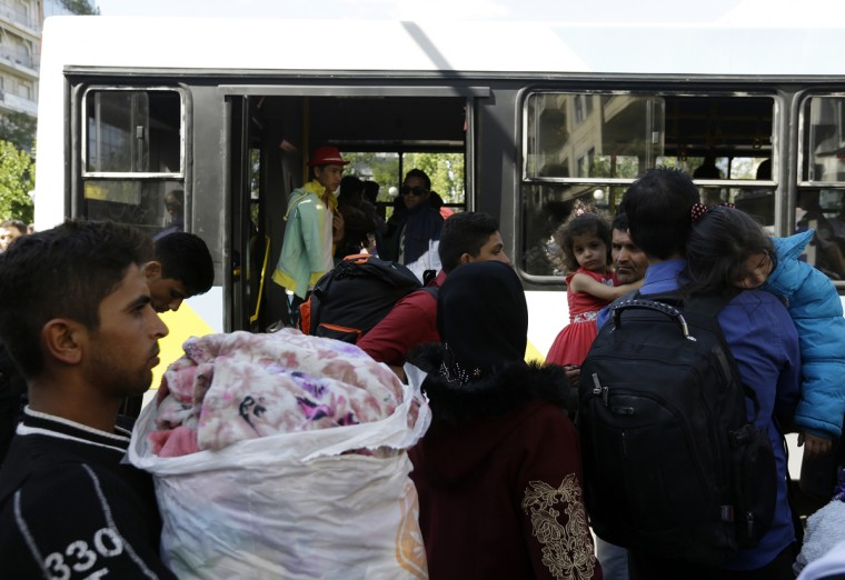 Migrants enter buses as they leave from Victoria square, where hundreds stay temporarily before trying to continue their trip to more prosperous northern European countries, in Athens on Thursday, Oct. 1, 2015. Authorities in Greece have reopened a disused Galatsi Olympic Hall as police escorted buses carrying about 500 people, mostly from Syria and Afghanistan. (AP Photo/Thanassis Stavrakis)