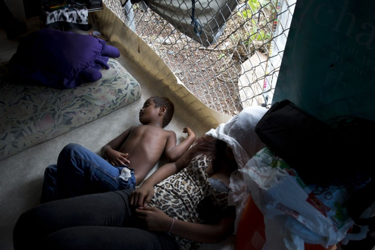 A boy and woman sleep in their makeshift tent at a homeless encampment in the Kakaako district of Honolulu. There are estimated 7,620 homeless people living on the streets in Hawaii. (AP Photo/Jae C. Hong)
