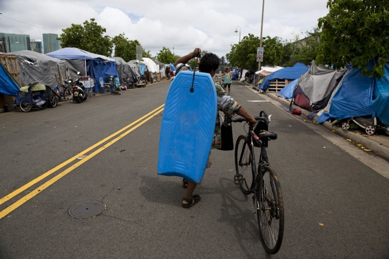 Lohe Akau, a 55-year-old homeless construction worker, carries his bodyboard through a homeless encampment in the Kakaako district of Honolulu. There are estimated 7,620 homeless people living on the streets in Hawaii. (AP Photo/Jae C. Hong)