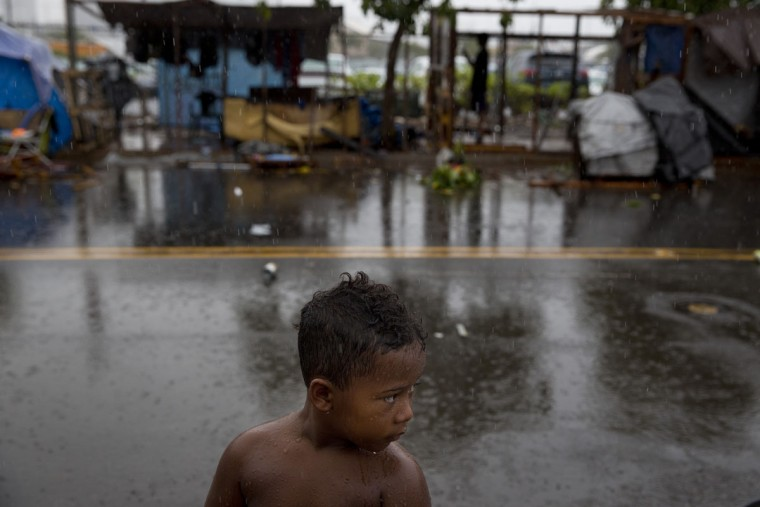 A boy stands in the rain in front of makeshift tents at a homeless encampment in the Kakaako district of Honolulu. Micronesians made up about a third of the Kakaako homeless encampment. Homelessness in Hawaii has grown in recent years, leaving the state with 487 homeless per 100,000 people, the nation's highest rate per capita, ahead of New York and Nevada, according to federal statistics. (AP Photo/Jae C. Hong)