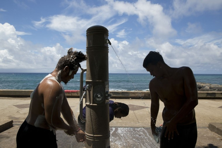 From left, John Tuilata, Tiare Talo and Roy Kalama, wash themselves using public showers in Kakaako Waterfront Park in Honolulu. The three live in a homeless encampment in Honolulu's Kakaako district. Homelessness in Hawaii has grown in recent years, leaving the state with 487 homeless per 100,000 people, the nation's highest rate per capita, ahead of New York and Nevada, according to federal statistics. (AP Photo/Jae C. Hong)