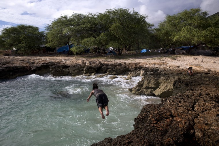 Kuulei Kealoha dives into the ocean to cool off in Waianae, Hawaii. The 40-year-old homeless woman is among nearly 300 people living in an encampment near the Waianae Boat Harbor. Homelessness in Hawaii has grown in recent years, leaving the state with 487 homeless per 100,000 people, the nation's highest rate per capita, ahead of New York and Nevada, according to federal statistics. (AP Photo/Jae C. Hong)