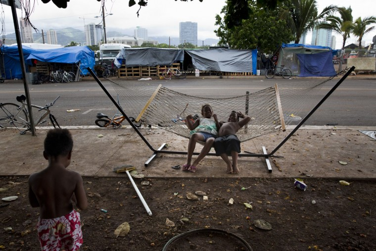 Two children rest on a hammock at a homeless encampment in the Kakaako district of Honolulu. Micronesians make up about a third of the encampment. Homelessness in Hawaii has grown in recent years, leaving the state with 487 homeless per 100,000 people, the nation's highest rate per capita, ahead of New York and Nevada, according to federal statistics. (AP Photo/Jae C. Hong)