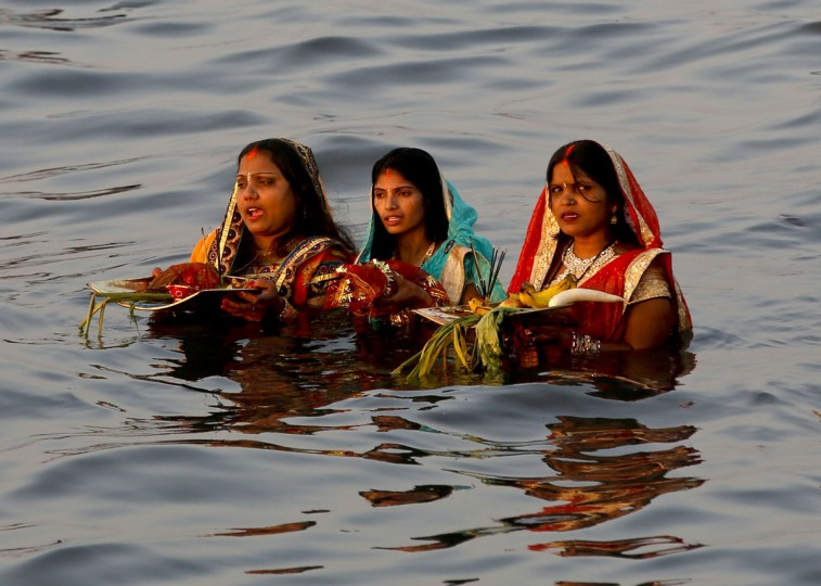 Hindu devotees offer prayers standing in the waters of the Arabian Sea at sun set during Chhath Puja festival in Mumbai, India, Tuesday, Nov 17, 2015. On Chhath, an ancient Hindu festival, rituals are performed to thank the Sun god for sustaining life on earth. (AP Photo/Rajanish Kakade)