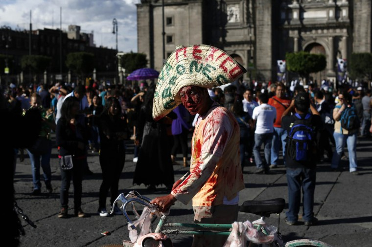 A man costumed as a zombie with a Mexican sombrero walks past in Mexico City's main Zocalo plaza, Monday, Nov. 2, 2015. People in costumes will stand at the plaza and earn some money as people take photos standing next to them during Day of the Dead and Halloween celebrations. (Dario Lopez-Mills/AP photo)