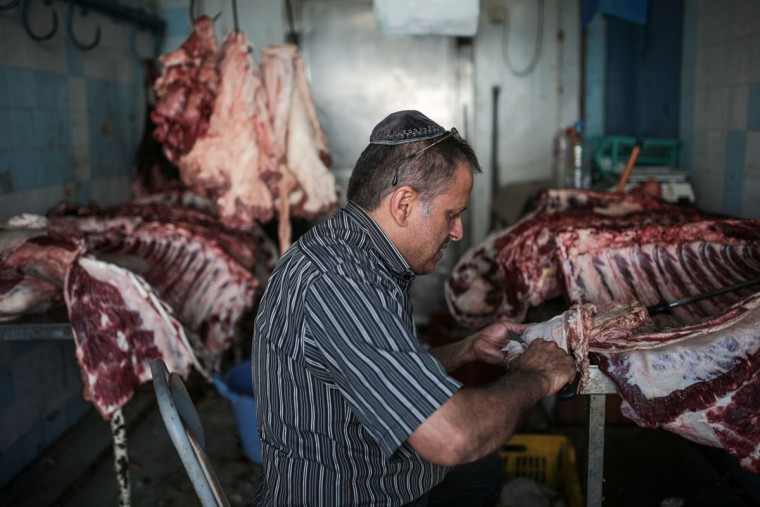 Char Haddad, 45, prepares meat in his kosher slaughterhouse at Hara Kbira, the main Jewish neighborhood on the Island of Djerba, southern Tunisia. The surrounding streets include a kosher butcher, a bakery that sells a traditional tuna-filled pastry known as ìbrikî and schools that teach lessons in Hebrew, French and Arabic. (AP Photo/Mosa'ab Elshamy)