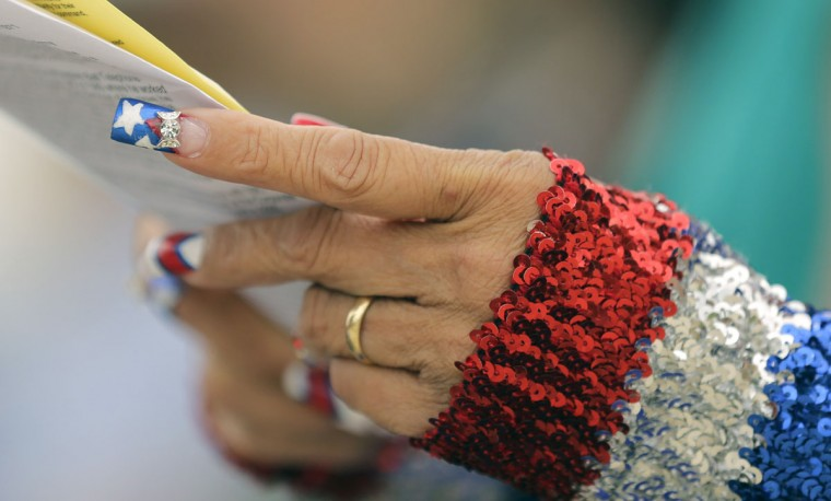 Dressed in red, white and blue and patriotic fingernails, Laura Allison attends a Veteran's Day observance at Fort Sam Houston National Cemetery, Wednesday, Nov. 11, 2015, in San Antonio. (AP Photo/Eric Gay)