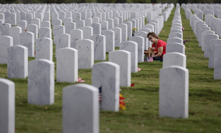 In observance of Veteran's Day, Oralia Ramirez visits the gravesite of her husband, an Army veteran, at Fort Sam Houston National Cemetery, Wednesday, Nov. 11, 2015, in San Antonio. (AP Photo/Eric Gay)