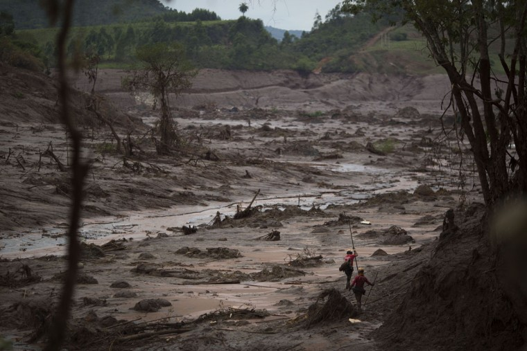 In this Sunday, Nov. 8, 2015 photo, rescue workers search for victims at the site where the town of Bento Rodrigues stood, after two dams burst on Nov. 5, in the state of Minas Gerais, Brazil. Search and rescue teams say they have found the bodies of six victims of the mud tide, while another 19 people remain missing. The mudflow continued through the week, eventually reaching a key river, where it has devastated wildlife and threatened the drinking water supply for hundreds of thousands of people downstream. (AP Photo/Felipe Dana)