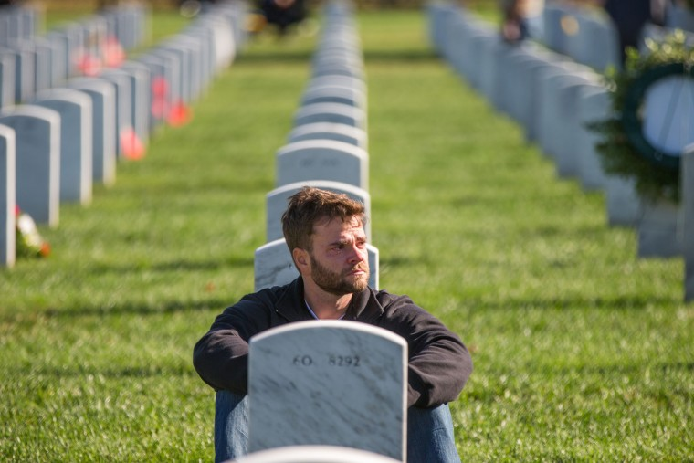 Army Sgt. Jason Bates of Baltimore, Md., spends time visiting with one of the 13 friends he lost while serving between 2006 and 2007, Wednesday, Nov. 11, 2015, on Veterans Day in Section 60 in Arlington National Cemetery in Arlington, Va. (AP Photo/Andrew Harnik)