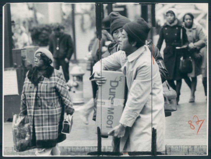 December 10, 1975 - Holiday shopper lugs big box on Howard and Lexington streets. (George H. Cook/Baltimore Sun)