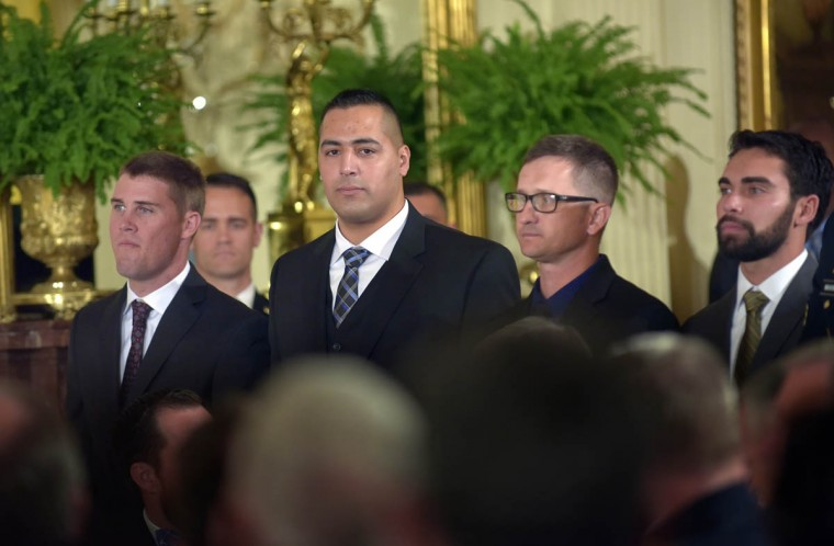 Members of retired Army Captain Florent Groberg's combat unit stand to be recognized for their heroism during Groberg's Medal of Honor ceremony in East Room ceremony at the White House. President Barack Obama presents Captain Florent A. Groberg, U.S. Army (Ret), the Medal of Honor for conspicuous gallantry for his courageous actions while serving as a Personal Security Detachment Commander for Task Force Mountain Warrior, 4th Infantry Brigade Combat Team, 4th Infantry Division during combat operations in Asadabad, Kunar Province, Afghanistan on August 8, 2012. He is the tenth living recipient to be awarded the Medal of Honor for actions in Afghanistan. (Algerina Perna, Baltimore Sun)