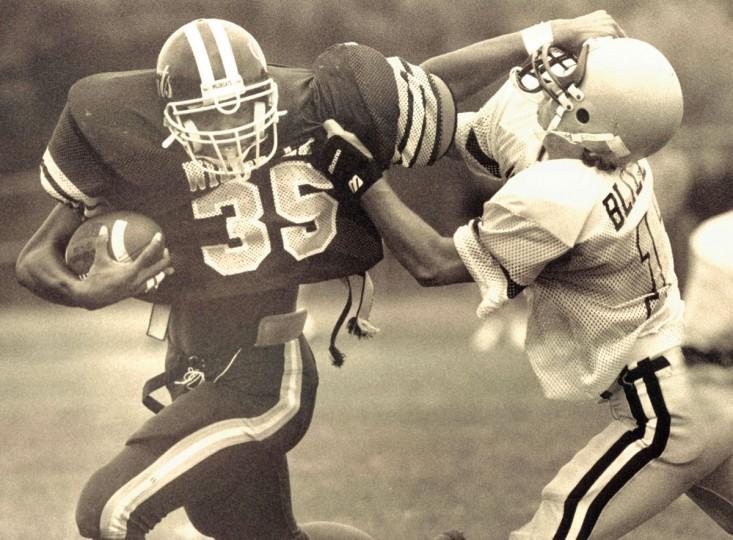 Mike Green of the Wilde Lake High School Wildcats hooks his thumb inot the helmet of Sotuh Carroll High School defender Brad Blizzard. (Jason Lee/Baltimore Sun, 1992)