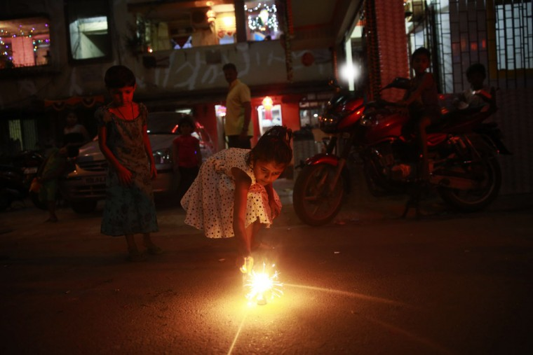 An Indian girl lights a firecracker to celebrate Diwali at a slum dwelling in Mumbai India, Wednesday, Nov. 11, 2015. Diwali, the festival of lights, is one of Hinduism's most important festivals dedicated to the worship of Lakshmi, the Hindu goddess of wealth. (AP Photo/Rafiq Maqbool)