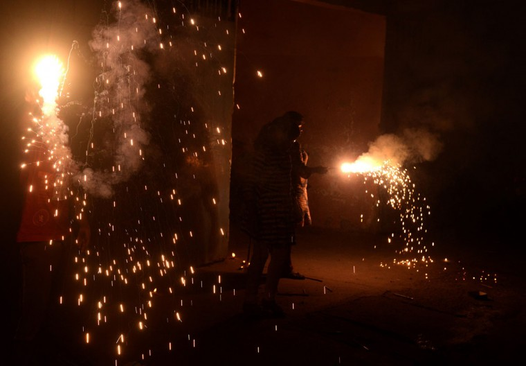 Indian people light firecrackers during celebrations of Diwali, the festival of lights, in Siliguri on November 11, 2015. Hindus decorate the entrance of their homes and business centers with marigold flowers, banyan trees and light fire crackers during the Diwali festival, which marks the victory of good over evil and commemorates the time when Hindu God Lord Rama achieved victory over Ravana. (DIPTENDU DUTTA/AFP/Getty Images)
