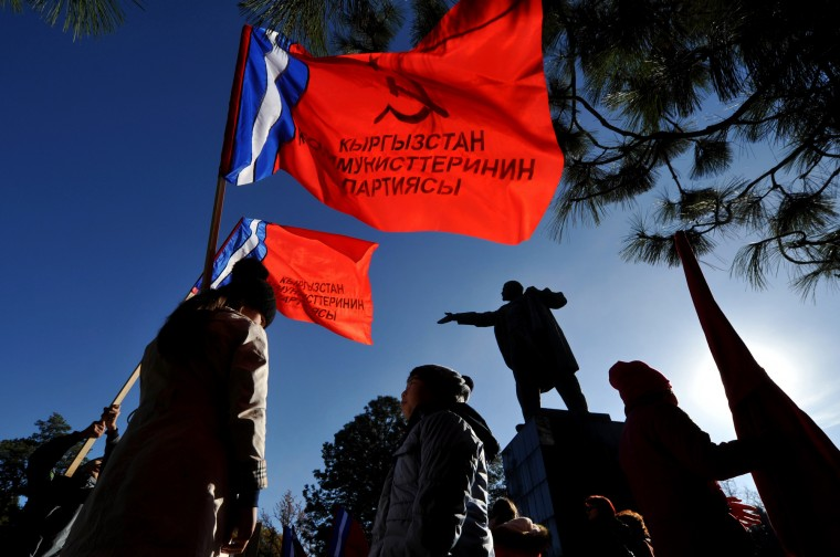 Kyrgyz communist party supporters hold red flags in front of monument to the Soviet Union founder Vladimir Lenin during a rally to mark the 98th anniversary of Russia's Bolshevik Revolution in central Bishkek on November 7, 2015. (Vyacheslav Oseledko/AFP-Getty Images)