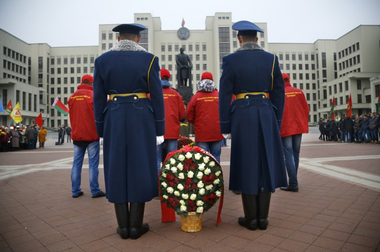 Belarusian honor guard soldiers stand as they prepare to lay flowers to the monument to Vladimir Lenin, Soviet founder during the celebration of the anniversary of the 1917 Bolshevik revolution in Minsk, Belarus, Saturday, Nov. 7, 2015. This is the state holiday in Belarus. A building of the Belarusian parliament is in the background. (AP Photo/Sergei Grits)