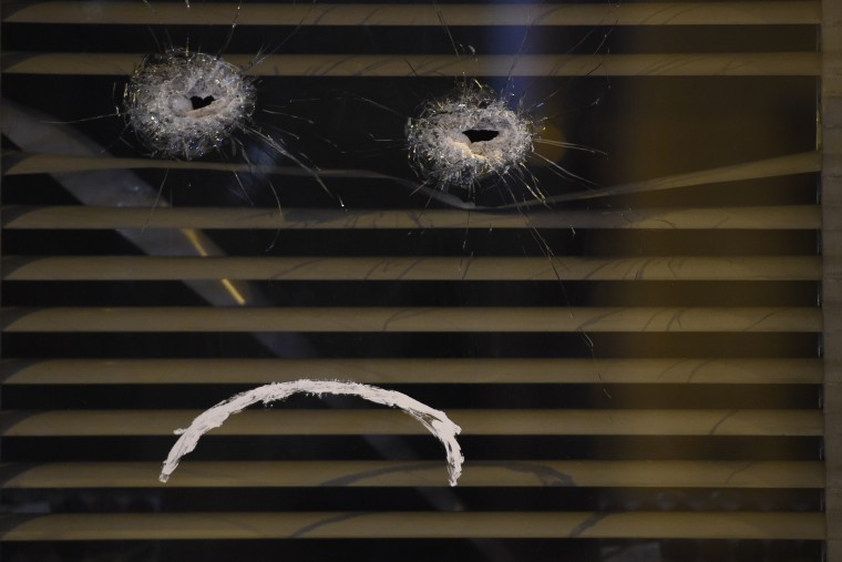 """Bullets holes from the shootings in Paris are used to make a sad smiley (emoticon) after someone drew a """"frowning mouth"""" on a window of the """"Belle Equipe"""" restaurant, the site of one of the attacks in Paris, as a tribute to the victims of the November 13 deadly attacks in Paris. Islamic State jihadists claimed a series of coordinated attacks by gunmen and suicide bombers in Paris that killed at least 129 people in scenes of carnage at a concert hall, restaurants and the national stadium. (Lionel Bonaventure/AFP-Getty Images)"""