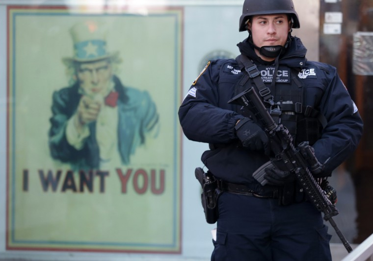 """A New York city police officer with the Strategic Response Group stands guard at the armed forces recruiting center in New York's Times Square, Saturday, Nov. 14, 2015. Police in New York say they've deployed extra units to crowded areas of the city """"out of an abundance of caution"""" in the wake of the attacks in Paris, France. A New York Police Department statement released Friday stressed police have """"no indication that the attack has any nexus to New York City."""" (AP Photo/Mary Altaffer)"""