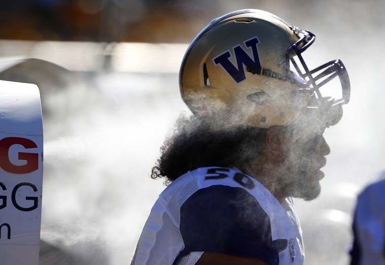 Washington's Vita Vea gets hit with moisture from a misting machines on the sidelines during the first half of an NCAA college football game against Arizona State Saturday, Nov. 14, 2015, in Tempe, Ariz. (AP Photo/Ross D. Franklin)