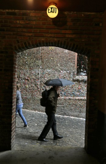 A pedestrian carries an umbrella while walking past Seattle's famous gum wall at Pike Place Market, Monday, Nov. 9, 2015. (AP Photo/Ted S. Warren)